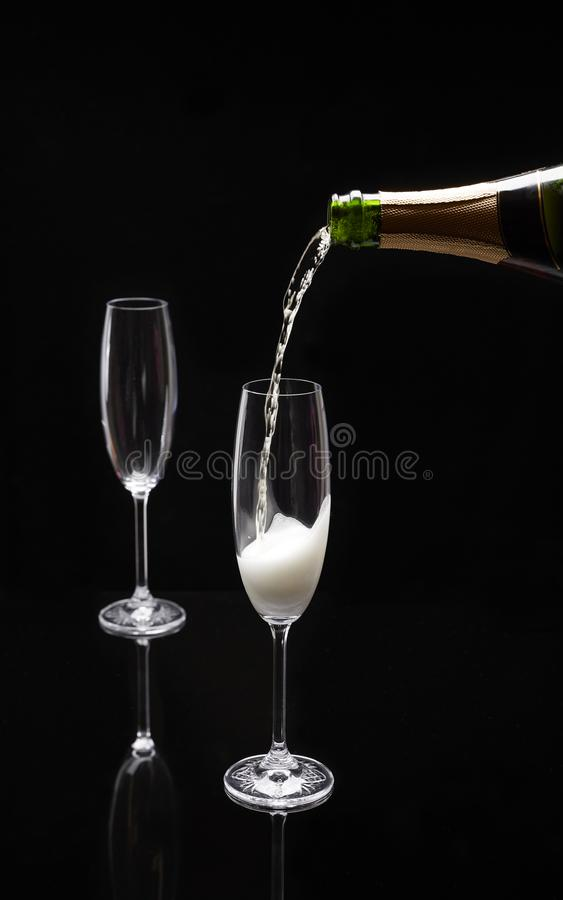 Champagne étant versée dans un verre sur un fond noir photo stock