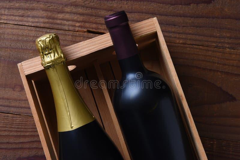 CHAMPAGNE και μπουκάλι κρασιού Cabernet - sauvignon σε ένα ξύλινο κιβώτιο δώρων στοκ εικόνα με δικαίωμα ελεύθερης χρήσης
