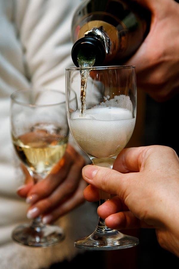 CHAMPAGNE χύνει από το μπουκάλι στο γυαλί Πλάγια όψη Φυσαλίδες αερίου σε ένα ποτήρι του κρασιού στοκ εικόνα με δικαίωμα ελεύθερης χρήσης