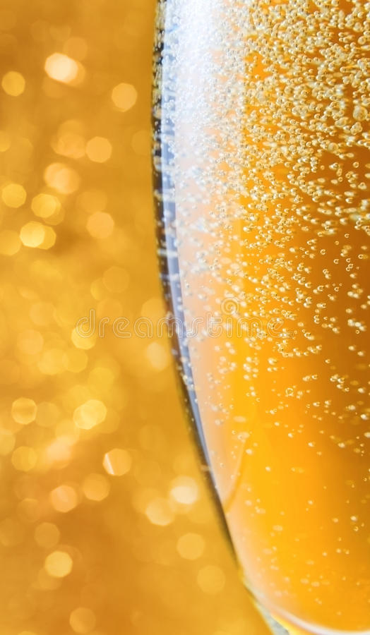 Champagne . Champagne in wineglass on a yellow background royalty free stock photo