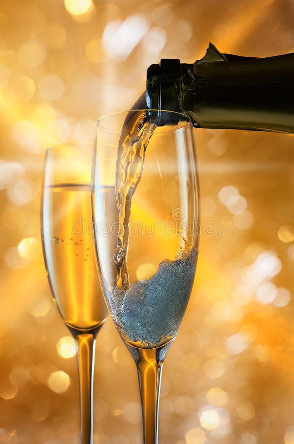 Champagne. In wineglass on a yellow background royalty free stock photo