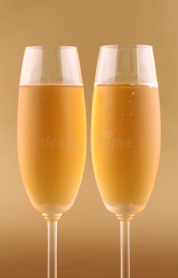 Champagne. Two glasses of champagne on gold background royalty free stock image