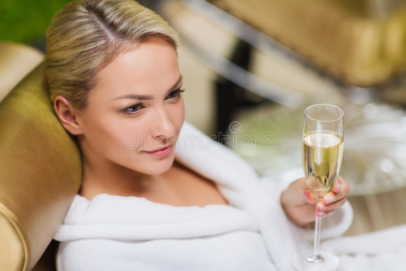 Champagne bevente della bella giovane donna alla stazione termale immagini stock libere da diritti