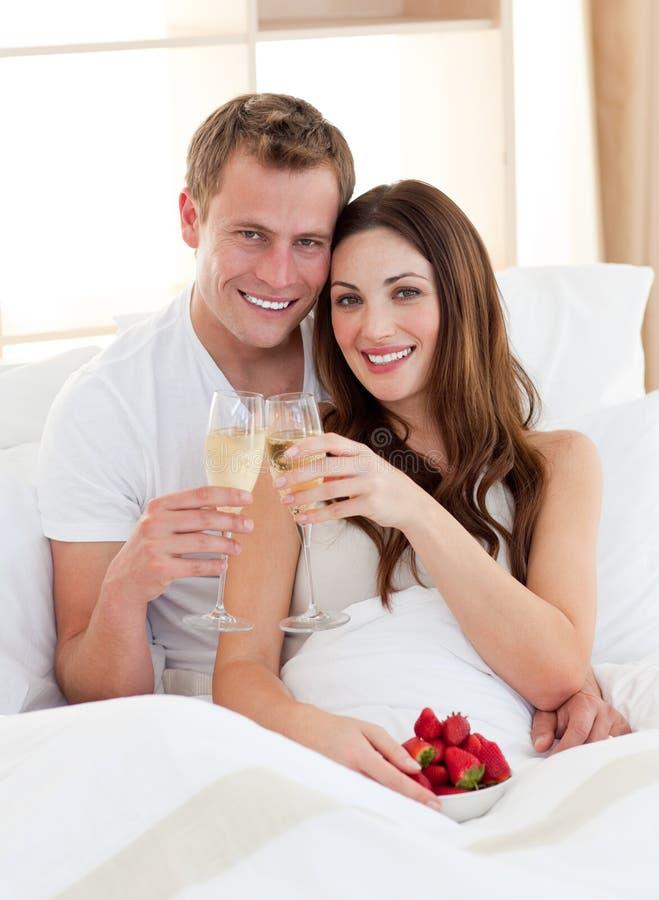 Champagne bevente Enamored delle coppie che si trova nella base fotografie stock