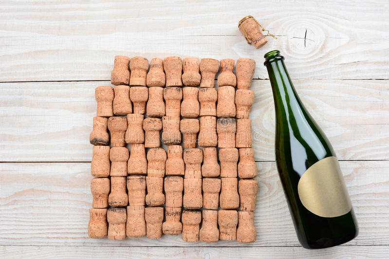 Champagne Blank Label and Corks. HIgh angle shot of a empty champagne bottle with blank label and corks. Closeup on a rustic white wood table. Horizontal format stock photography