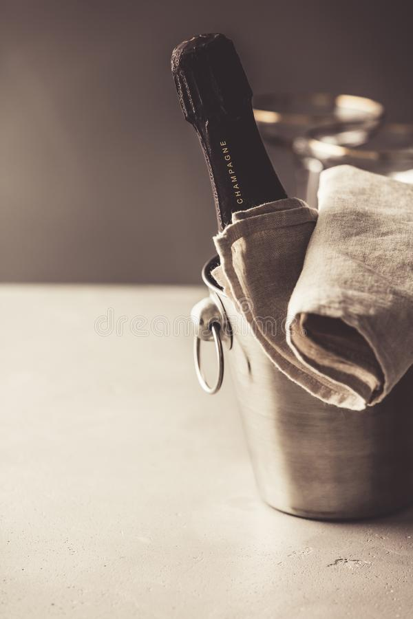 Champagne bottle in bucket and glasses on concrete background stock image