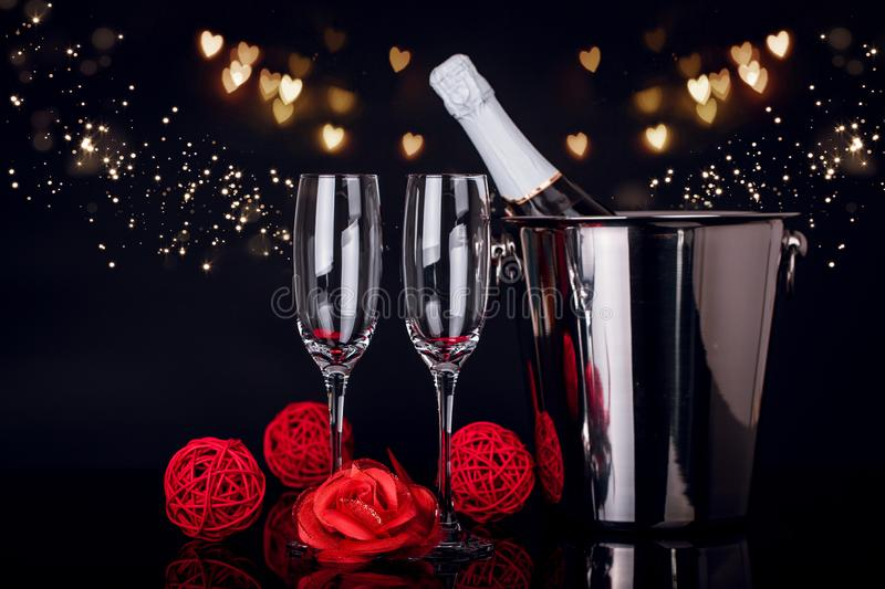 Champagne bottle in bucket, two wine glasses and red rose royalty free stock images