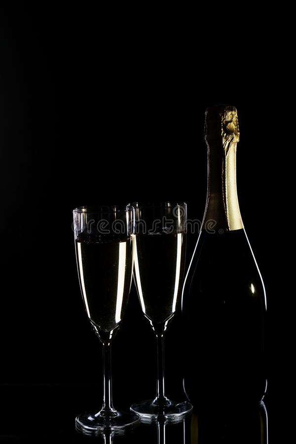 Champagne bottle and champagne glasses. In low key royalty free stock photos