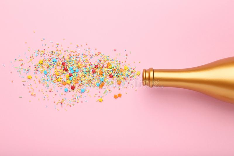 Champagne bottle with sprinkles. Champagne bottle with colorful sprinkles on pink background stock photography