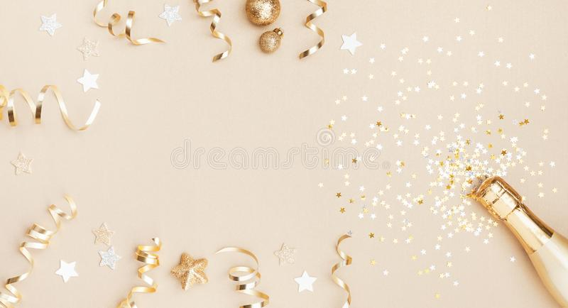 Champagne bottle with confetti stars, holiday decoration and party streamers on gold festive background. Christmas flat lay. Champagne bottle with confetti stars royalty free stock images