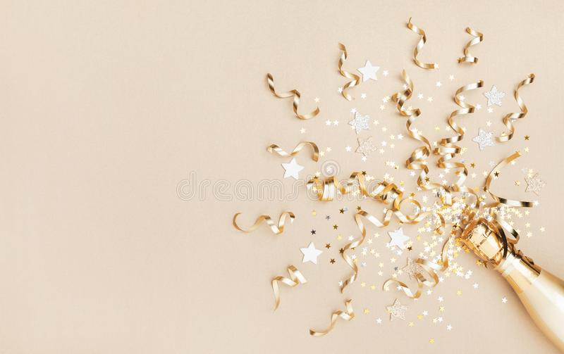 Champagne bottle with confetti stars and party streamers on gold festive background. Christmas, birthday or wedding. Flat lay royalty free stock photo