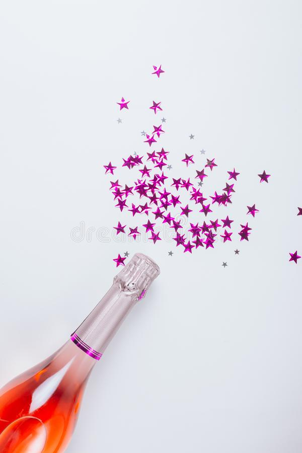 Champagne bottle with confetti stars on white background royalty free stock photos
