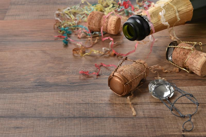 Champagne bottle confetti and streamers with corks strewm on the floor, the aftermath of a party.  royalty free stock photo