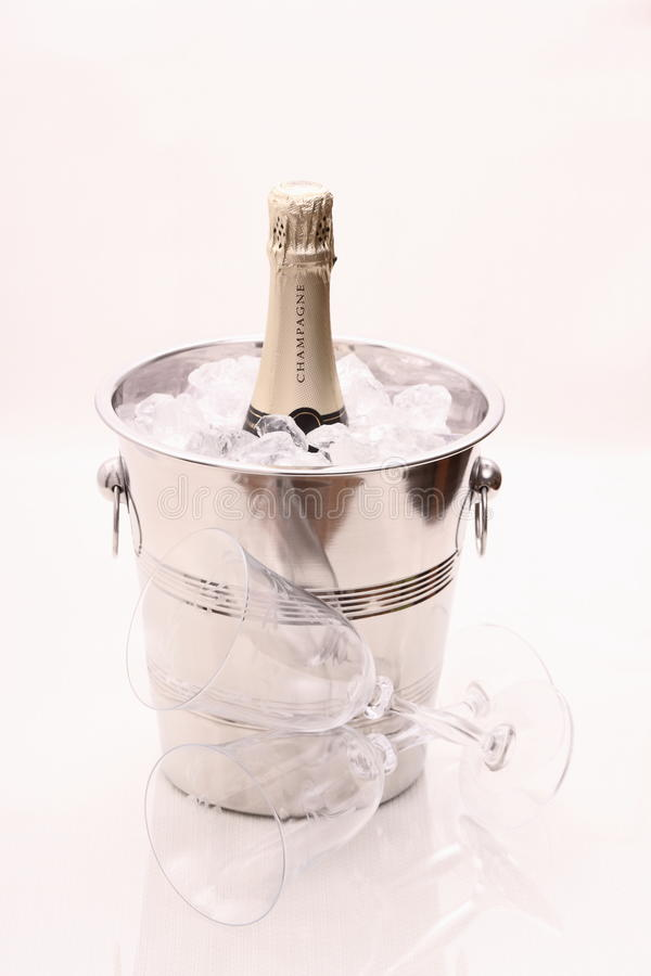 Champagne bottle in cooler and two champagne glasses royalty free stock photography