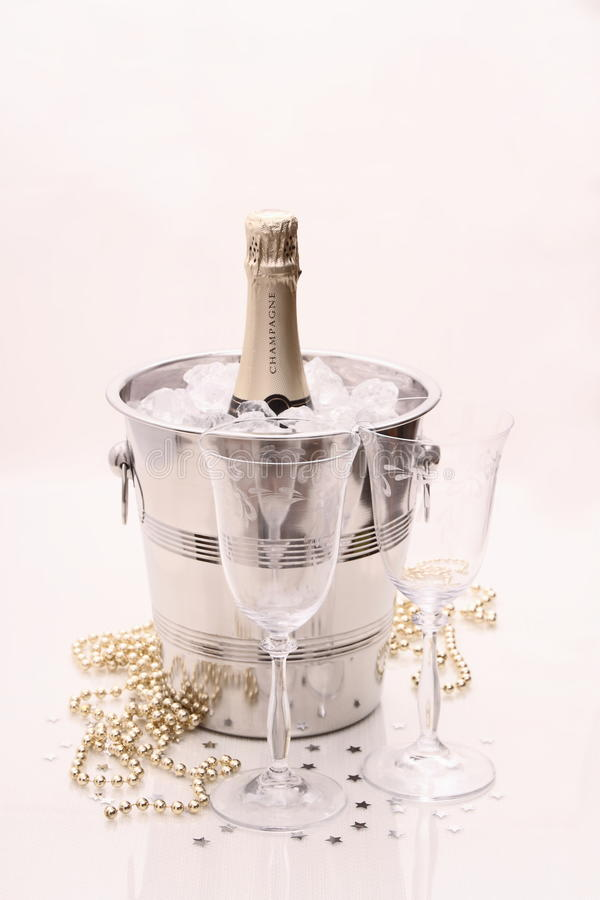 Champagne bottle in cooler, two champagne glasses royalty free stock photography
