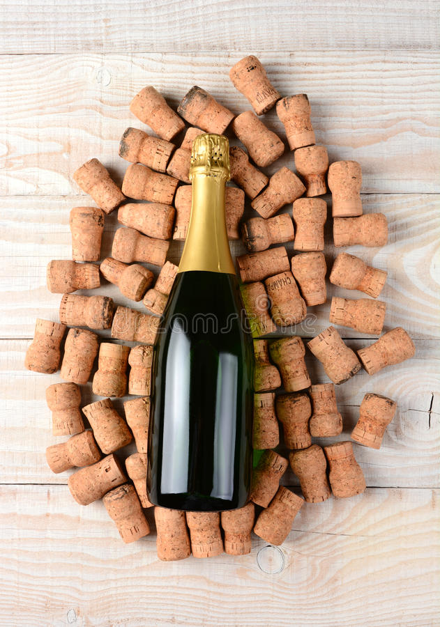 Champagne Bottle and Corks. High angle shot of an champagne bottle laying on its side and surrounded by old used corks. Horizontal format on a rustic white wood royalty free stock photography