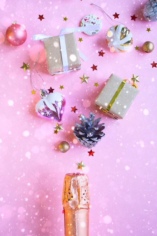 Champagne bottle with different christmas decoration on pink background. New year concept. Flat lay stock image