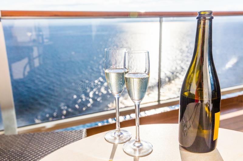 Champagne bottle and flutes glasses on luxury cruise travel for honeymoon holidays. Boat at sea on vacation sunset with royalty free stock images