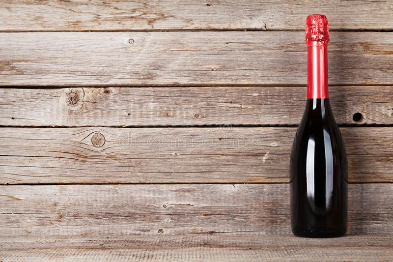 Champagne bottle. In front of wooden wall. With space for your text stock photos