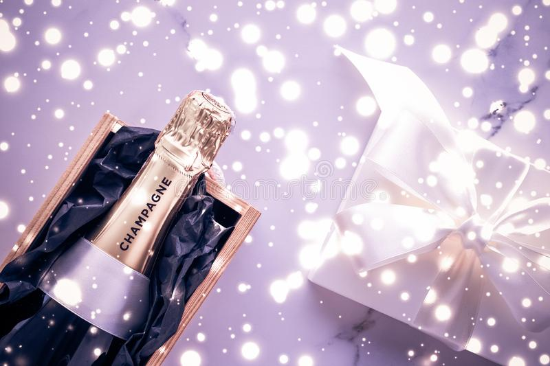 Champagne bottle and gift box on purple holiday glitter, New Years, Christmas, Valentines Day, winter present and luxury product stock photos