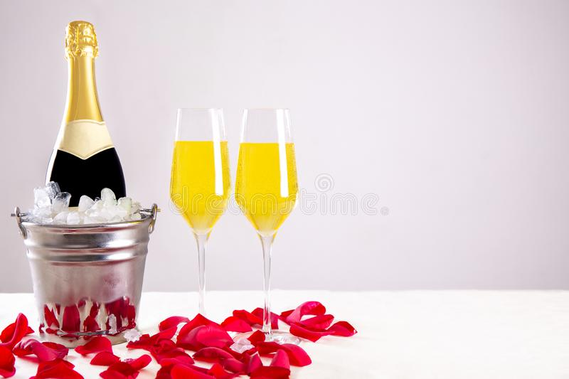 Champagne bottle with glasses and red roses stock photo
