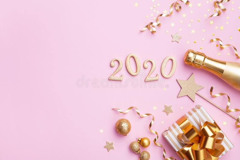 Champagne bottle, golden gift or present box, 2020 number and confetti on pink background top view.Christmas and New Year flat lay. Champagne bottle, golden gift royalty free stock image