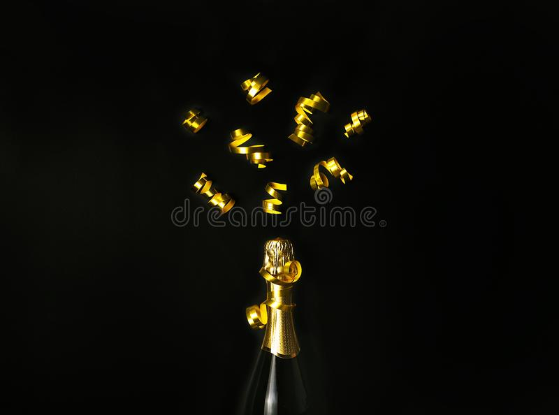 Champagne bottle with golden party streamers on black background. Flat lay style. Celebration concept. stock images
