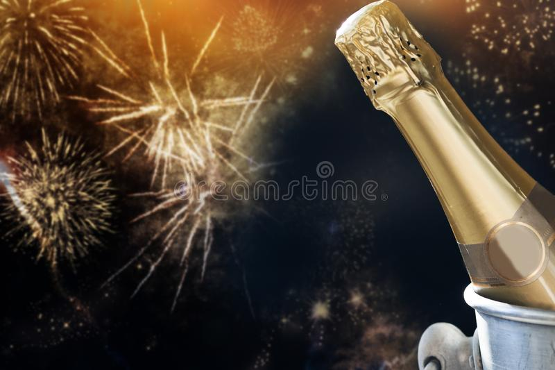 champagne bottle ready to bring in the New Year - holiday lights and fireworks in the background stock photos