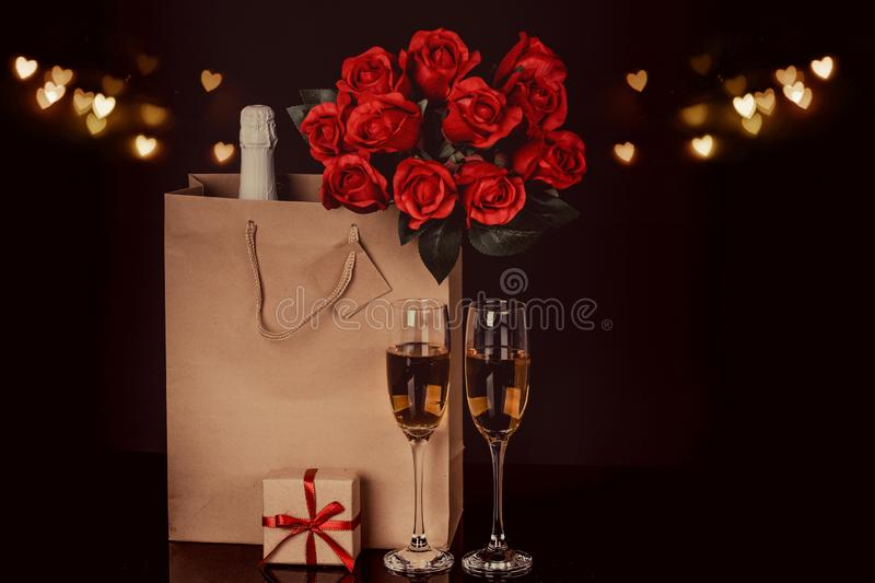Champagne bottle, red roses in a paper bag and two wine glasses stock photo