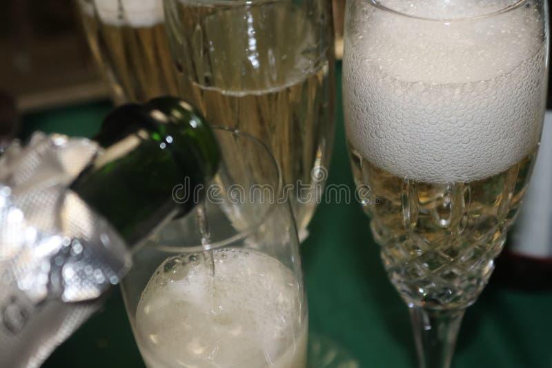 Champagne bouillonne dans un verre cristal avec plus de champagne étant renversé photo stock