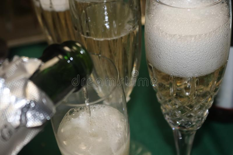Champagne bubbles in a crystal glass wth more champagne being poured stock photo