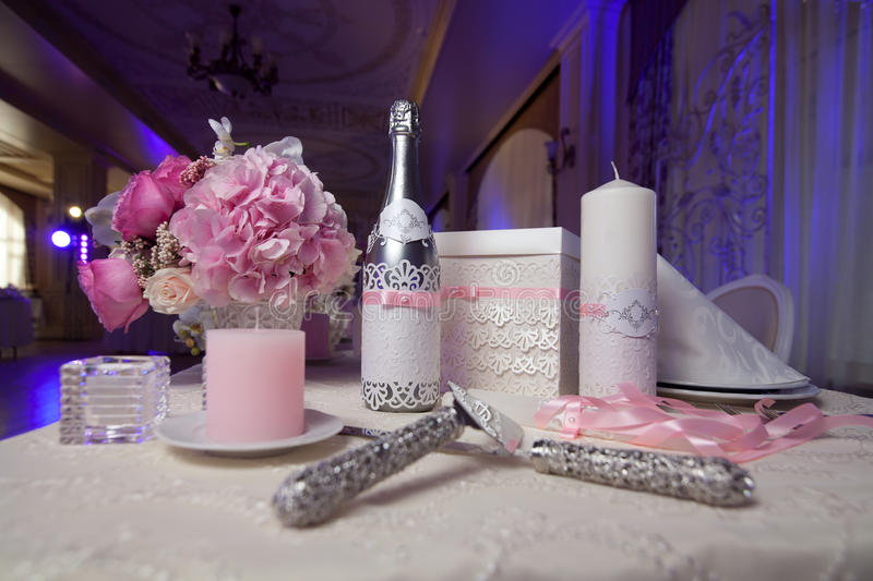 Champagne, candles and flowers as wedding decorations. The blade and the knife to cut the cake. Selective focus royalty free stock image