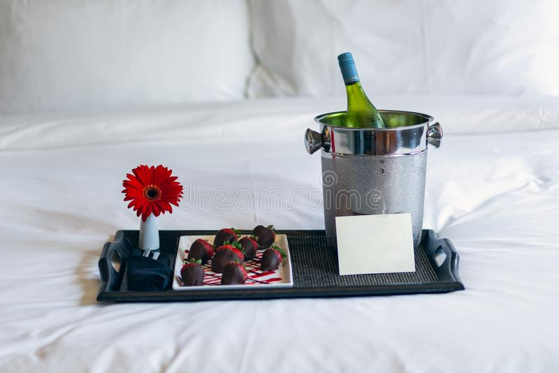 Champagne and chocolate strawberries on bed royalty free stock photography