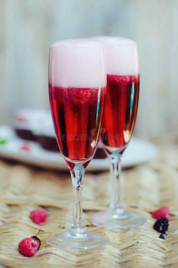 Champagne-cocktails met frambozen voor een romantische avond op een houten lijst Roze vloeibare kleur, glazen met bellen stock afbeelding