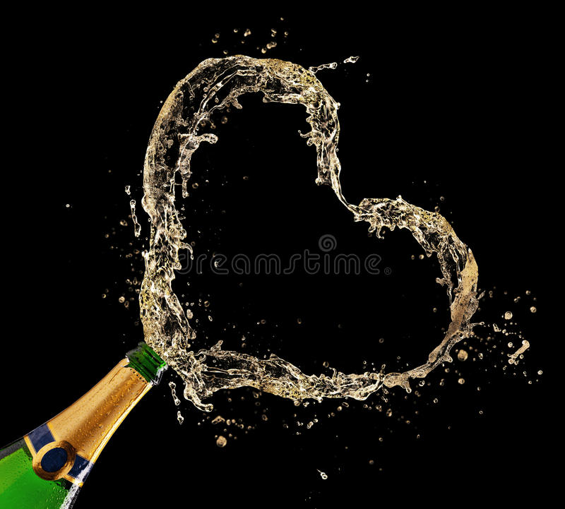 Champagne concept. Bottle of champagne with heart shape splash on black background stock images