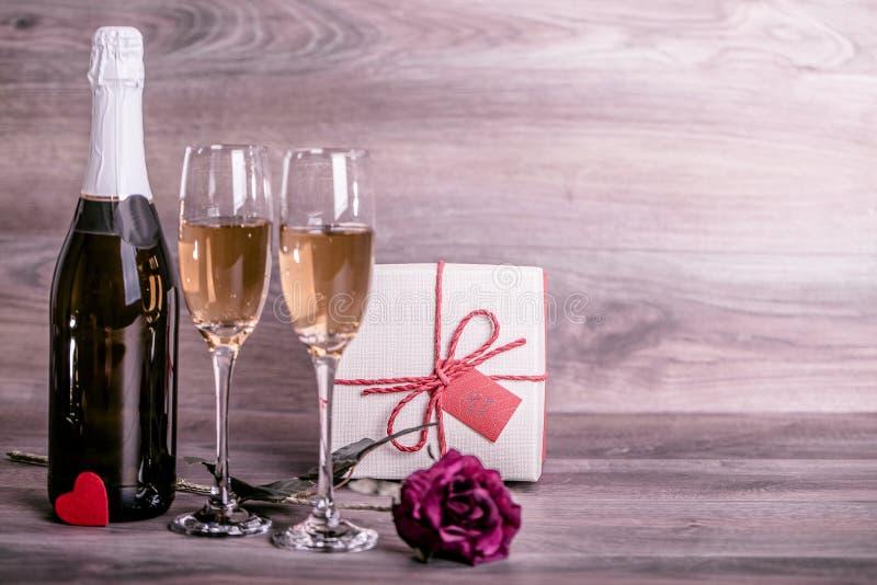 Champagne, cor-de-rosa e um presente na tabela imagem de stock royalty free