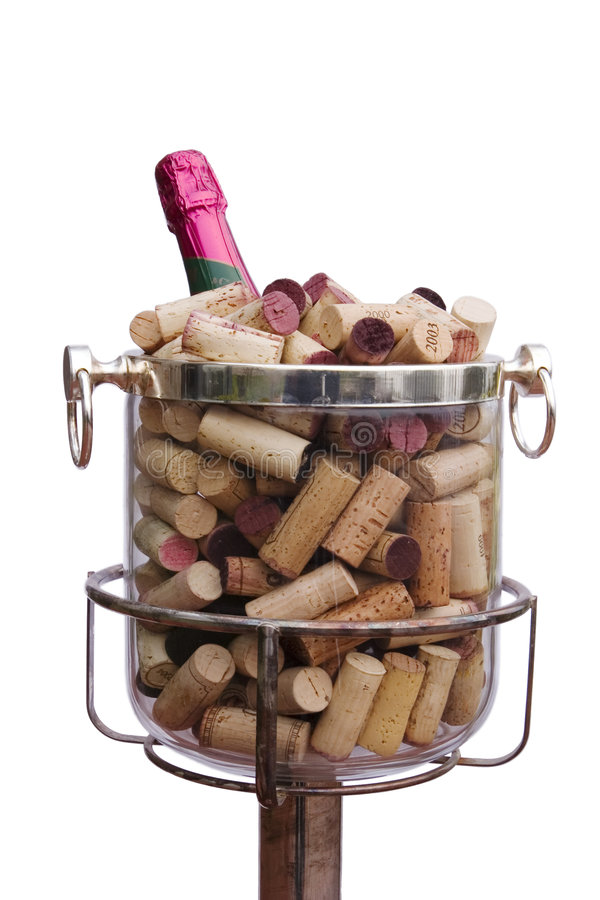 Champagne With Corks. A bottle of champagne with a bright pink foil labelchilling in an ice bucket filled with corks pulled from a variety of bottles. This is a royalty free stock images