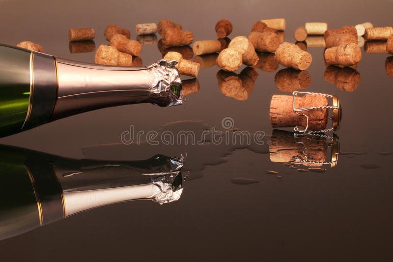 Champagne and corks. On a black glass table royalty free stock image