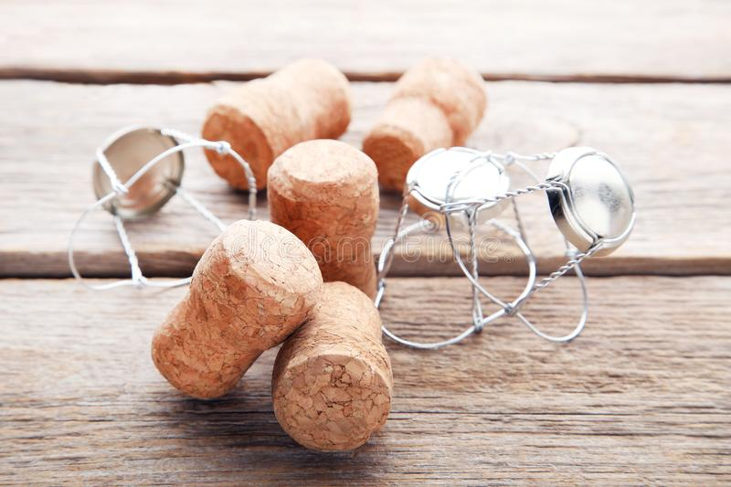 Champagne corks with caps. On grey wooden table stock images