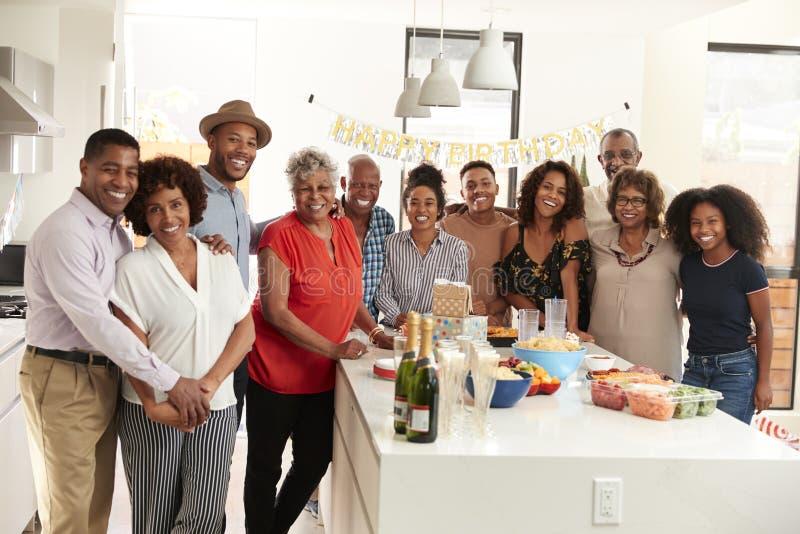 Champagne d'apertura invecchiato medio dell'uomo afroamericano da celebrare a casa con la sua famiglia di tre generazioni fotografia stock libera da diritti