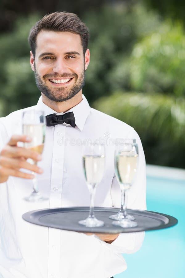 Champagne de offre de serveur heureux photo stock