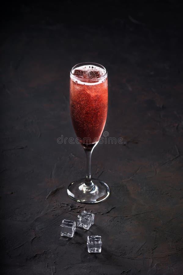Champagne della mimosa del cocktail con ghiaccio in vetri su un fondo scuro Copi lo spazio fotografia stock libera da diritti