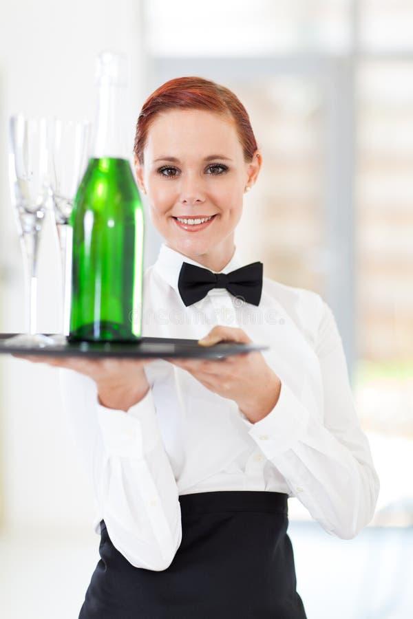 Champagne della tenuta della cameriera di bar fotografie stock