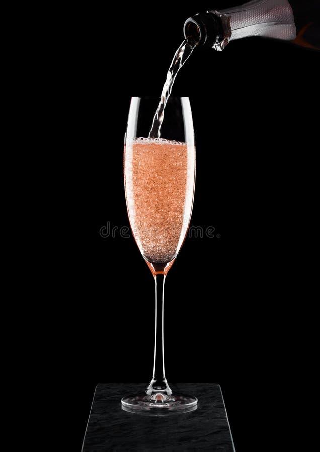 Champagne di versamento della rosa di rosa dalla bottiglia a vetro sul bordo di marmo nero su fondo nero Spazio per testo immagini stock