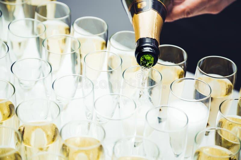 Champagne di versamento nei vetri che stanno sulla tavola Evento di banchetto fotografia stock