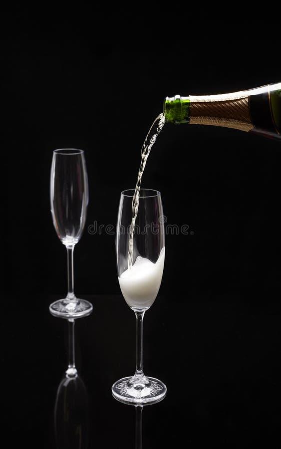 Champagne, die in ein Glas auf einem schwarzen Hintergrund gegossen wird stockfoto