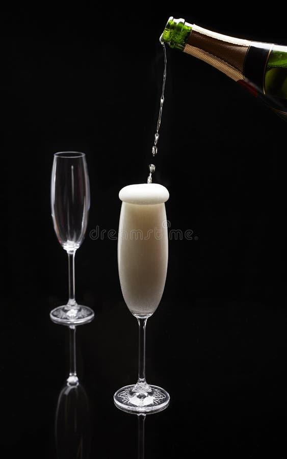 Champagne, die in ein Glas auf einem schwarzen Hintergrund gegossen wird lizenzfreie stockfotos