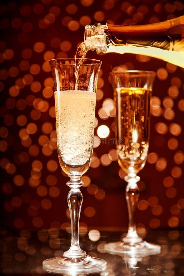 Champagne, die in elegantes Glas gießt stockfoto