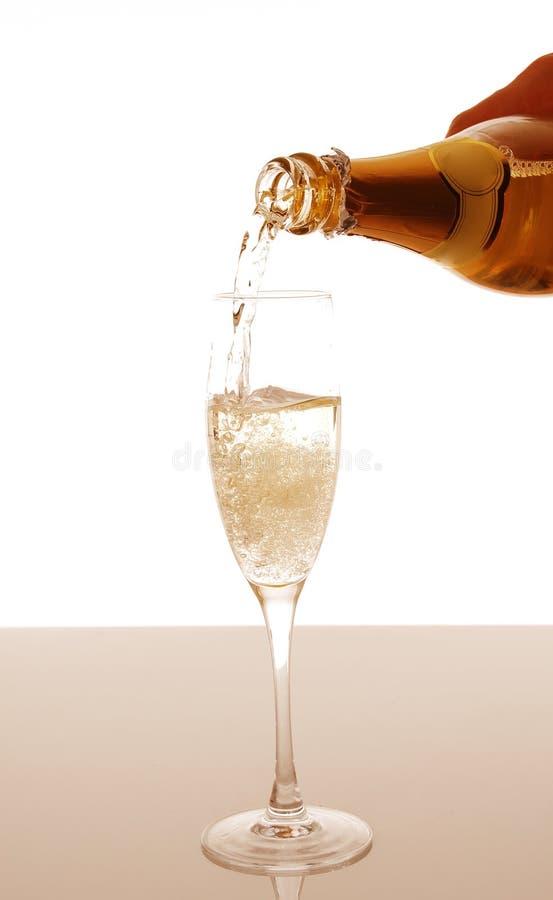 Champagne, die in elegantes Glas gießt stockbild