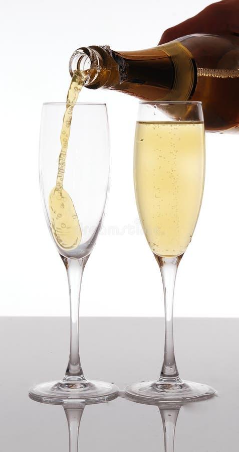 Champagne, die in elegantes Glas gießt lizenzfreie stockfotografie